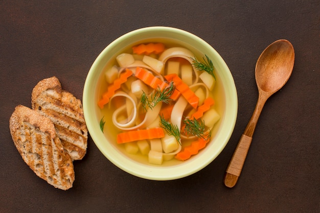 Top view of winter vegetables soup with toast and spoon