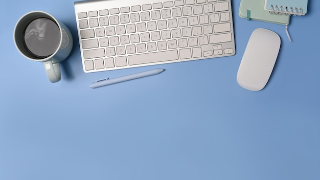 Беспроводная клавиатура, кофейная чашка и ноутбук взгляд сверху на синем фоне.