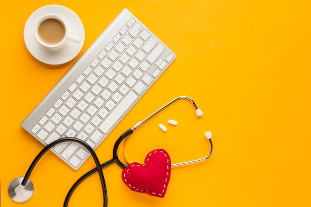Top view of wireless keyboard; tablets; coffee cup; stethoscope; stitched toy heart; above yellow backdrop