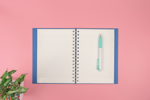 Top view with  of book  pen overhead on pink pastel background, flat lay
