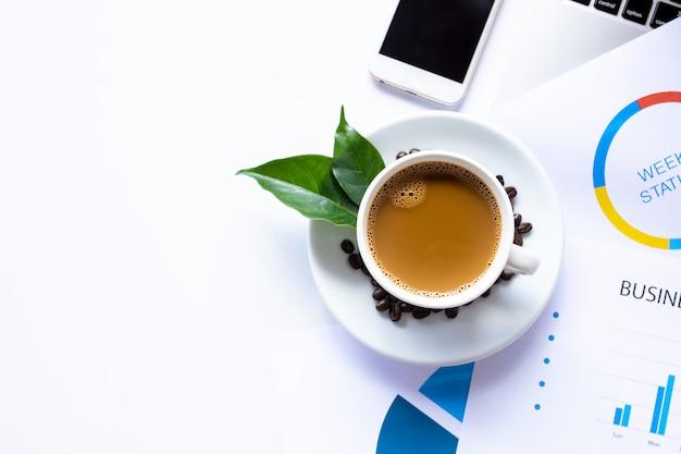 コーヒーカップとコーヒー豆、ワークフロードキュメント、コンピューター、スマートフォンと白いオフィスデスクテーブルのコピースペースのトップビュー