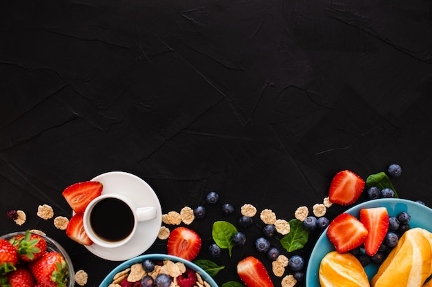 Top view with copy space on top of healthy breakfast on black wooden background