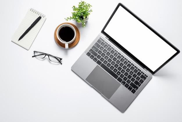 机の上にラップトップの空白の白い画面で上面図。