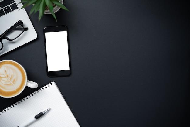 Вид сверху с ноутбуком, мобильным телефоном, чашкой кофе, карандашом, карандашом и очками на черном