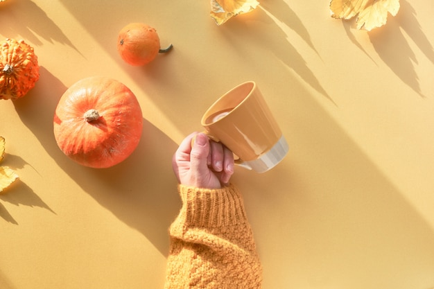Top view with long shadows and copy-space. yellow paper flat lay with female hand holding cup of coffee, decorative pumpkins, quince and maple leaves.