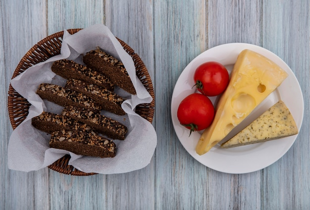 Top view with slices of black bread in a basket with cheeses and tomatoes on a plate  on a gray background