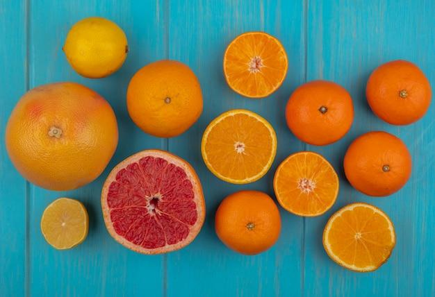 Vista dall'alto con fette e arancia intera e pompelmo su sfondo turchese