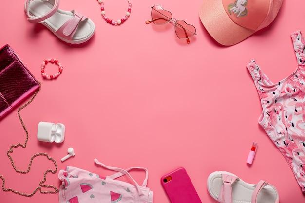 ピンクのバックに夏服子供服とアクセサリー電話ヘッドフォン口紅の上面図...