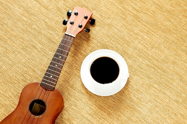 Top view with ukulele on the floor there are cup of coffee is placed