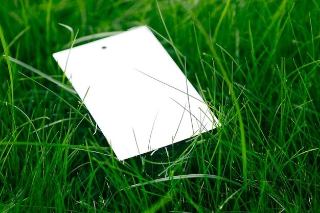 Вид сверху с макетом пустой бирки из белого картона газонной зеленой травы с биркой для логотипа.