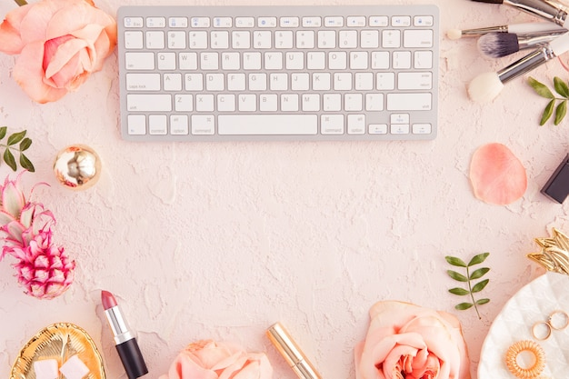 Top view of woman beauty blogger working desk with computer keyboard and laptop, decorative cosmetic, flowers and palm leaves