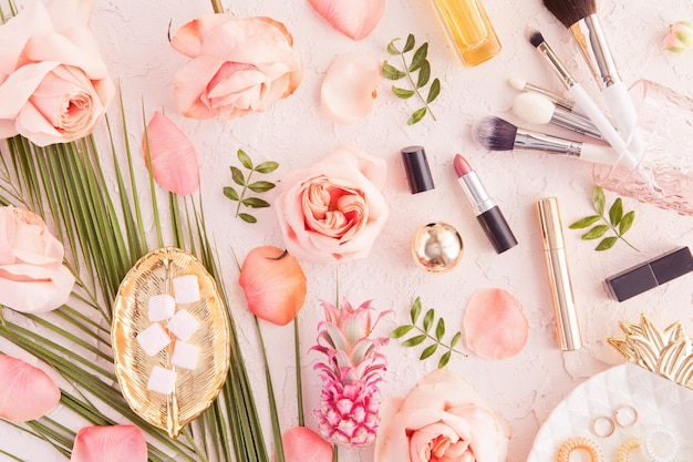 Top view of woman beauty blogger working desk with decorative cosmetic, flowers and palm leaves, leaf plate, envelope on pink pastel table