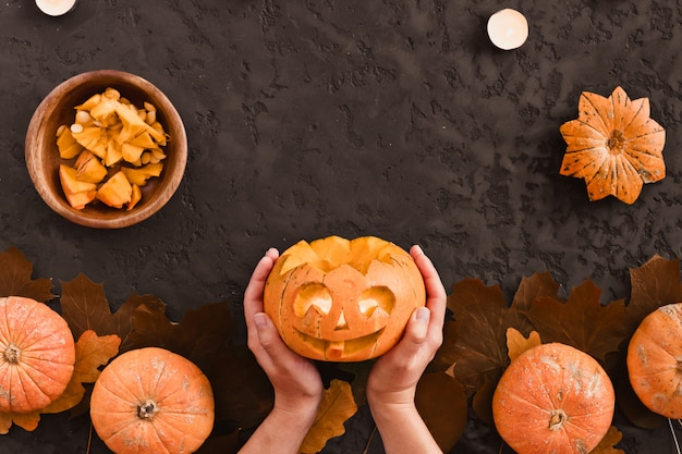 Top view of woman carves face of a jack-o'-lantern