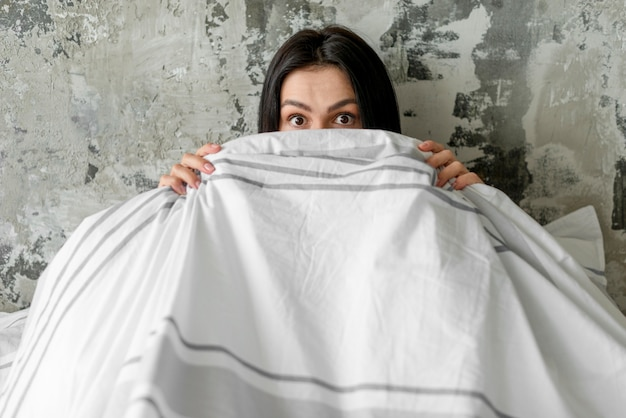 Top view woman covering her face with blanket