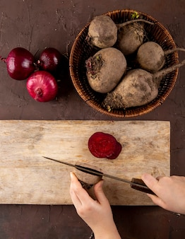 Top view woman cuts beets on a blackboard with fresh beets in a basket with red onions