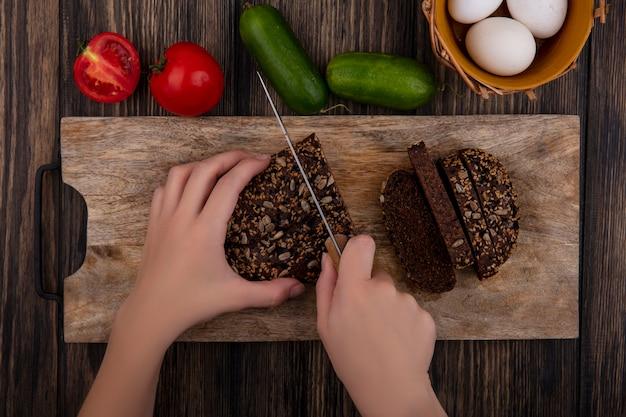 Вид сверху женщина режет черный хлеб на подставке с помидорами, огурцами и куриными яйцами на деревянном фоне