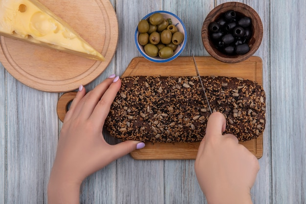 Вид сверху женщина режет черный хлеб на разделочной доске с сыром маасдам, черными и зелеными оливками на сером фоне