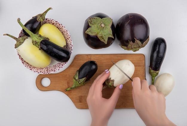 Vista dall'alto donna taglia melanzane in bianco e nero su un tagliere con un coltello e in un piatto su uno sfondo bianco