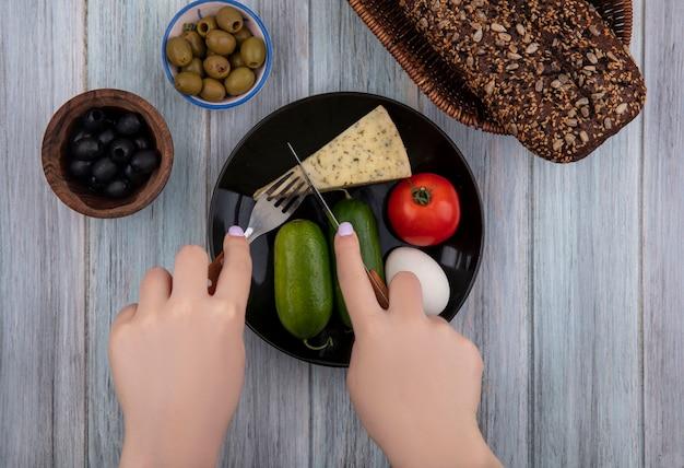 上面図の女性は、灰色の背景に黒と緑のオリーブとプレートにきゅうりのトマトの卵でチーズをカットします