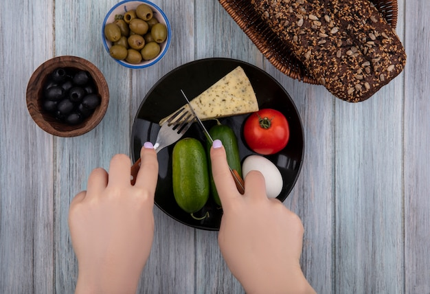 Vista dall'alto la donna taglia il formaggio con l'uovo di pomodoro cetrioli su un piatto con olive nere e verdi su sfondo grigio