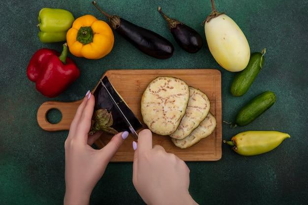 Vista dall'alto donna taglia melanzane su un tagliere con peperoni e cetrioli su uno sfondo verde