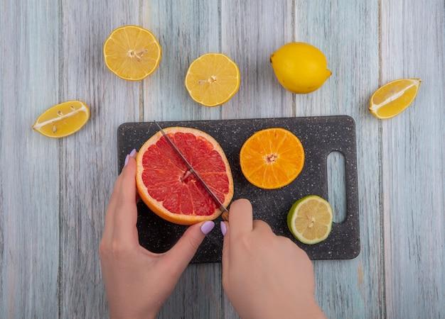 Vista dall'alto donna taglia spicchi di pompelmo con arancia lime e limone su un tagliere su uno sfondo grigio