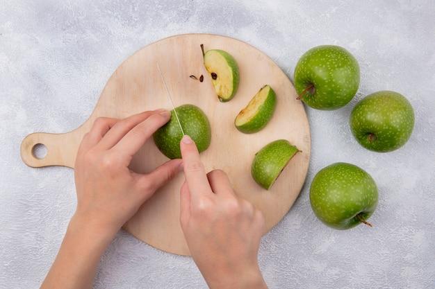 Donna vista dall'alto taglia le mele verdi su un tagliere su uno sfondo bianco