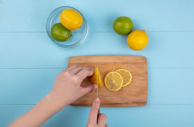 La donna di vista superiore taglia il limone su una tavola con calce su un tavolo blu