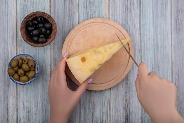 Vista dall'alto la donna taglia il formaggio maasdam su supporto con olive nere e verdi su sfondo grigio