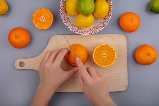 Top view  woman cuts oranges on cutting board with lemons and limes in plate on gray background