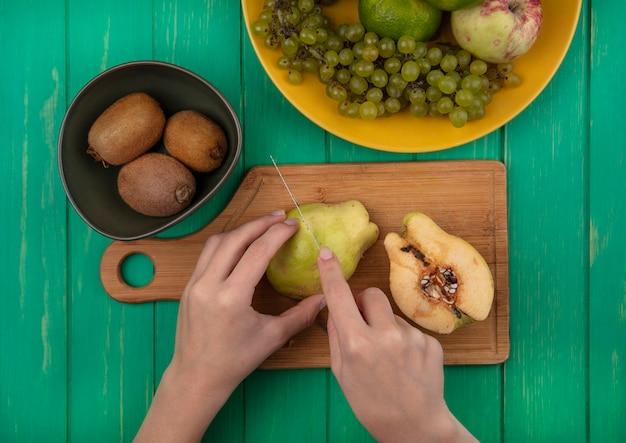 Vista dall'alto la donna taglia la pera su un tagliere con kiwi e mandarini su una parete verde