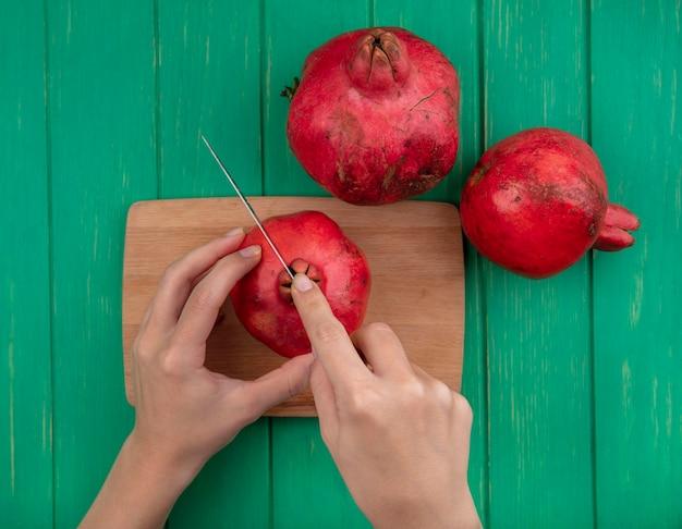 상위 뷰 여자 녹색 벽에 커팅 보드에 석류를 인하