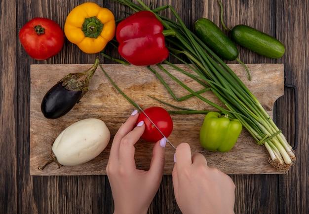 La donna di vista superiore taglia il pomodoro con le melanzane bianche e nere delle cipolle verdi su un tagliere con i peperoni colorati su un fondo di legno