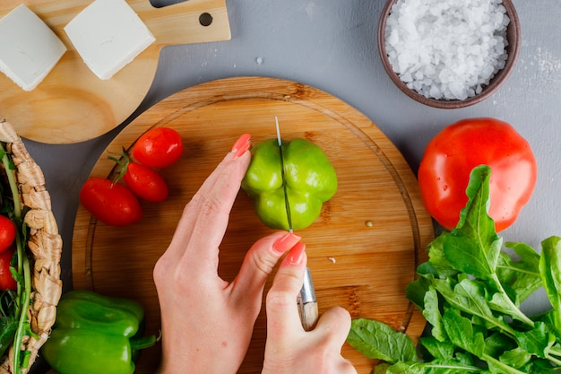Top view woman cutting green pepper on cutting board with tomatoes, salt, cheese on gray surface
