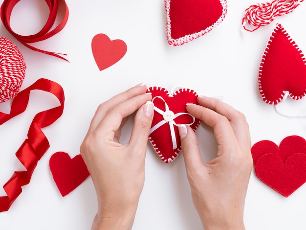 Top view of woman decorating red hearts
