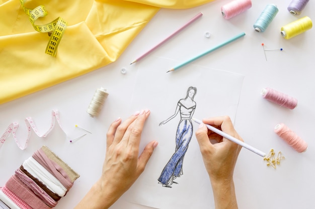 Top view of woman designing garment to sew