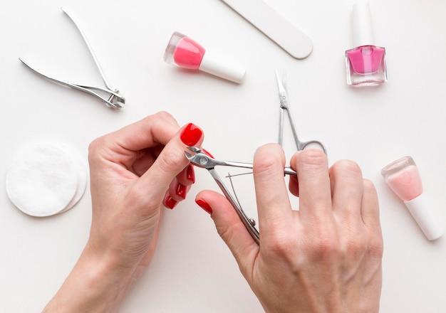 Женщина взгляд сверху делая маникюр ногтя