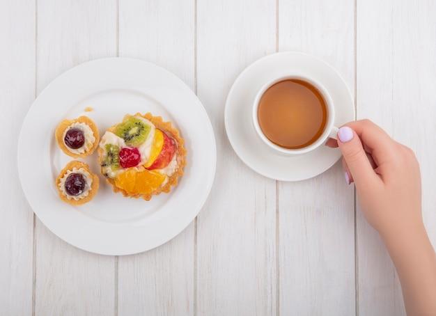 白い背景の上のプレートにタルトとお茶を飲む上面図の女性