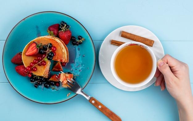 トップビューの女性は青いテーブルにイチゴの赤と黒スグリとパンケーキとお茶のカップを飲む