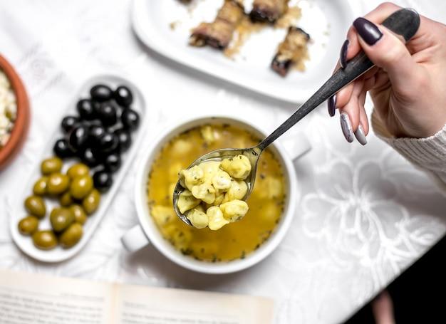 Вид сверху женщина ест традиционное азербайджанское блюдо душбара с оливками