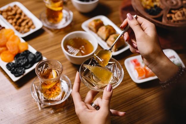 トップビューの女性がお茶を飲みながらスイカジャムを食べる