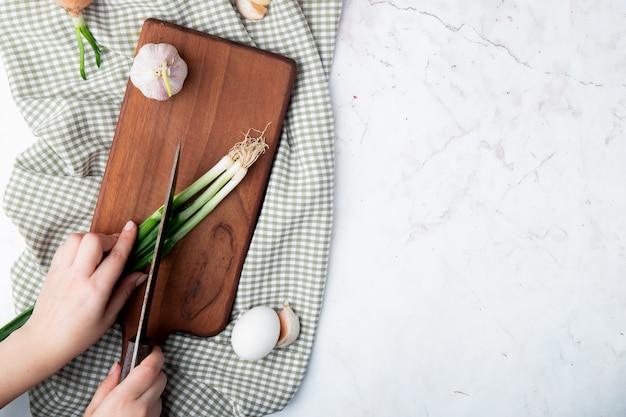 Top view of woman hand cutting green onion on cutting board with garlic and egg on white background with copy space
