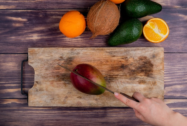 Top view of woman hand cutting mango with knife on cutting board and coconut tangerine avocado on wooden background