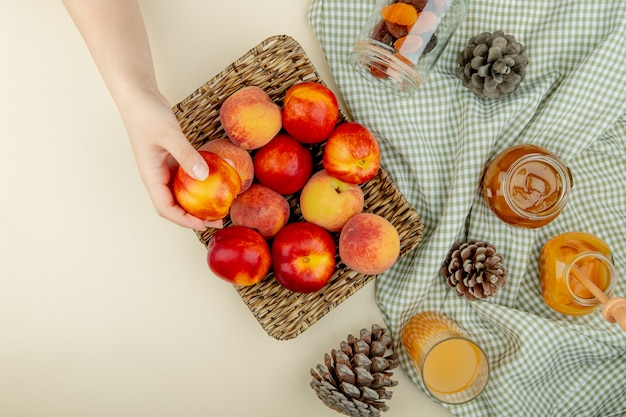 Top view of woman hand holding basket plate of peaches with plum jam peach juice raisins and pinecones on cloth on white surface