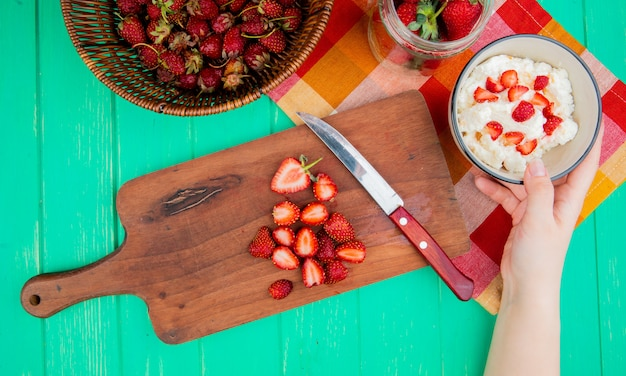 Top view of woman hand holding bowl of cottage cheese with strawberries and knife on cutting board and basket of strawberries on green surface