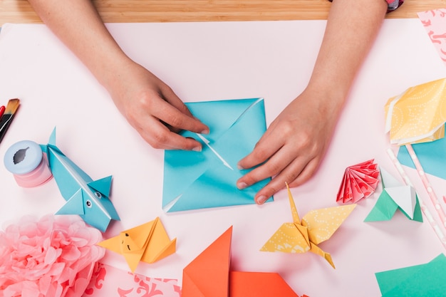 Top view of woman hand making origami craft over table