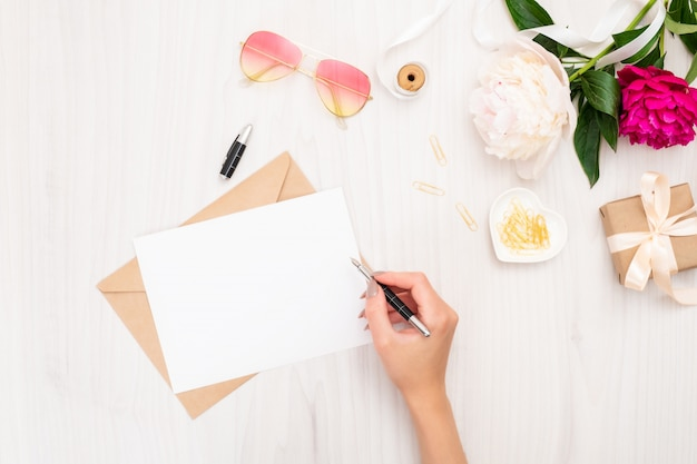 결혼식 초대 카드 또는 연애 편지를 쓰는 상위 뷰 여자 손.
