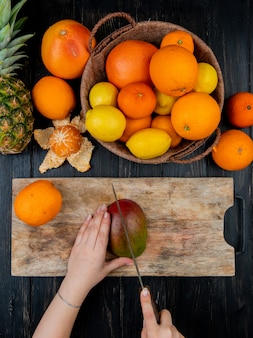 Top view of woman hands cutting mango with knife on cutting board and citrus fruits as orange lemon tangerine pineapple on wooden table