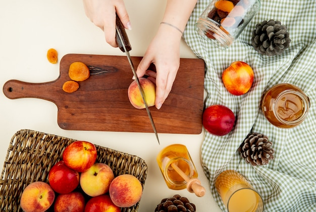 Top view of woman hands cutting peach with knife and dried plums on cutting board with jams and juice raisins and pinecones around on white surface