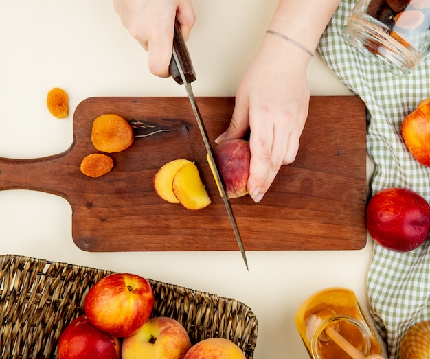 Top view of woman hands cutting peach with knife and dried plums on cutting board with plum jam and raisins around on white surface